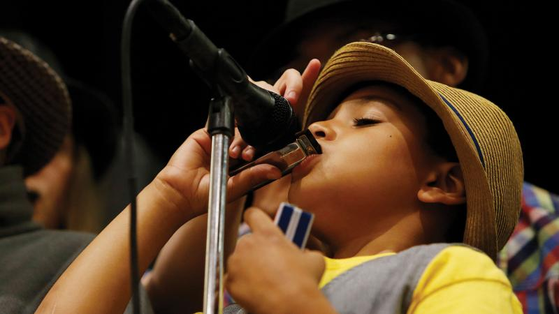 A student plays a harmonica into a microphone during the ABP's program