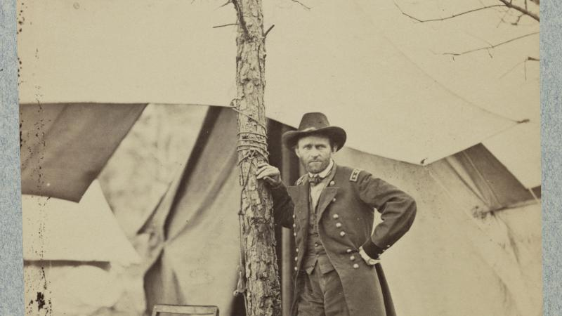 Grant at his headquarters in Cold Harbor, Virginia, in June 1864. Leaning on a tree, in front of several tents