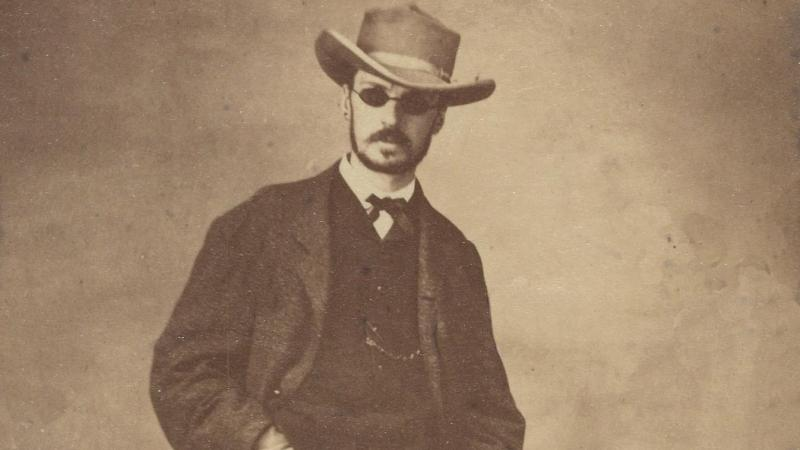 William James in 1865, wearing sunglasses and a hat