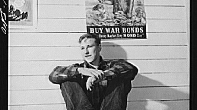 Black and white photo of young man sitting on table, war poster behind him