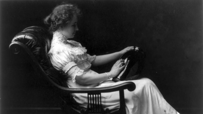 Black and white photo of Helen Keller sitting in chair