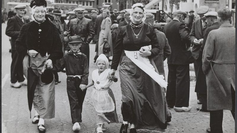 Black and white photo of two women and two children, dressed in folklore costumes, in Markden
