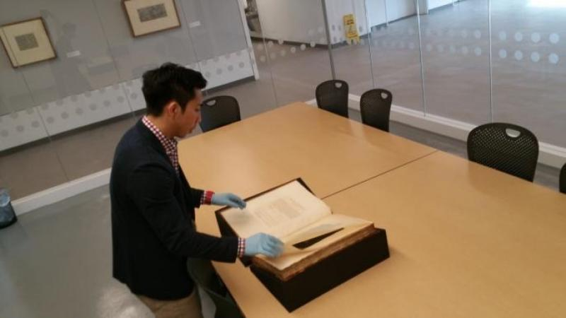 Individual with gloves on examining a large antique book
