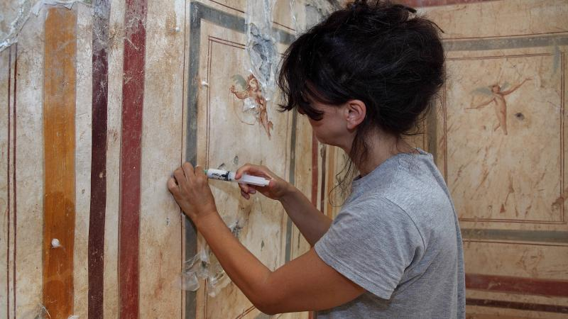 Woman restoring a wall painting