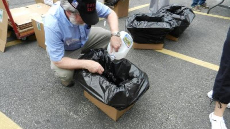 A man crouching over a cardboard box, where he is inserting the negative of a photograph