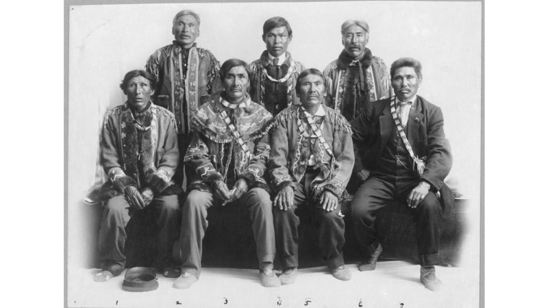 Group of Native American men, half seated, half standing up