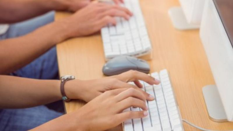 Photo of two people typing on keyboards
