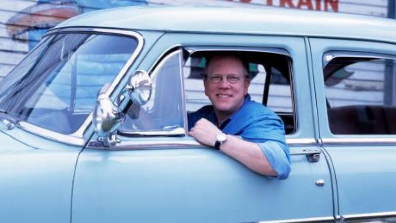 Photo of Nick Spitzer, host of American Routes, in a blue car