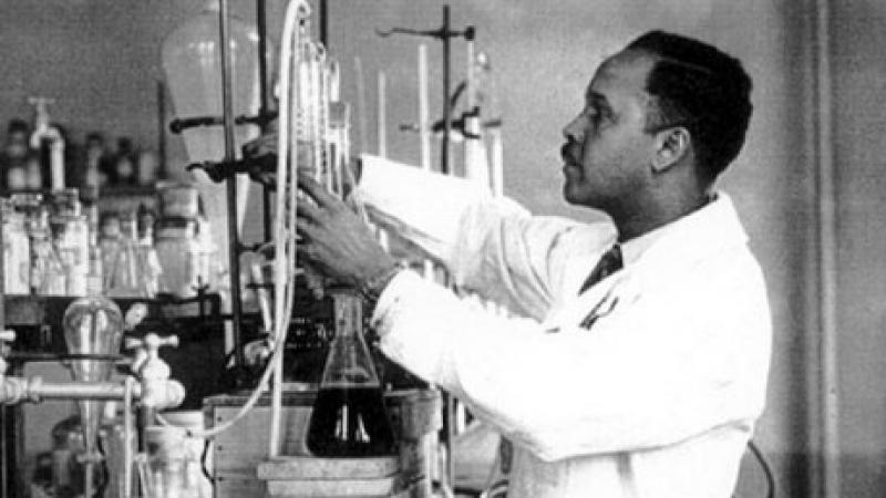 Photograph of Percy Julian in his lab, measuring chemicals in a beaker