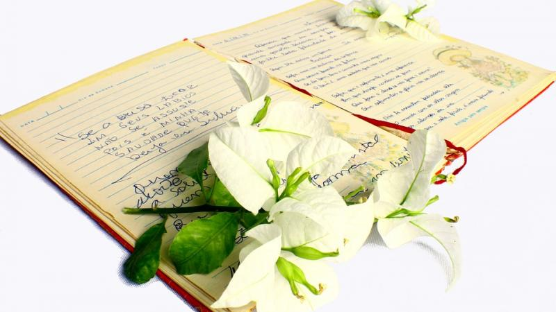 Photo of an open book of poetry, with a bunch of lilies laid on top of the book