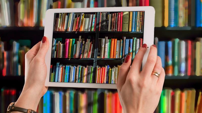 Two hands holding up a tablet in front of a large bookshelf