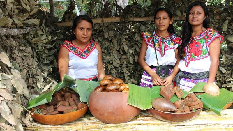 Three native oaxacan women standing behind bowls of food