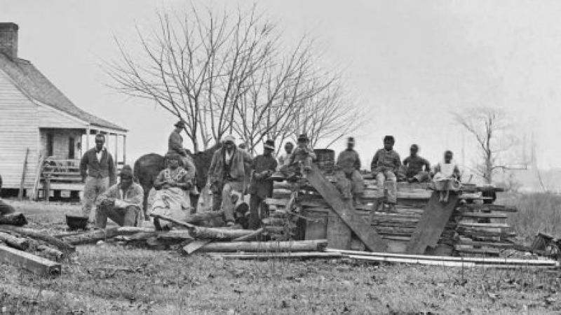 Black and white photo of a group of black boys sitting atop a large pile of lumber.
