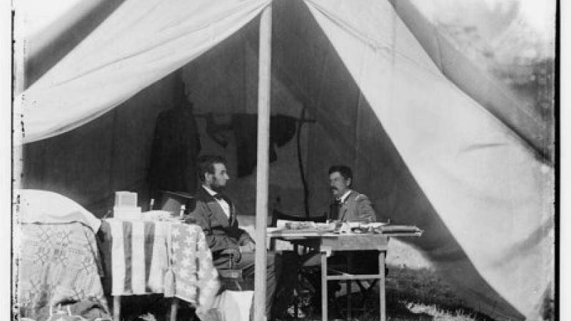 Black and white photo of Abraham Lincoln sitting with McClellan inside a general's tent.