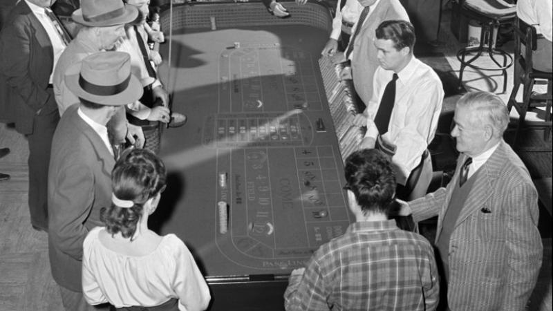 black and white photo of people gathered around a gaming table