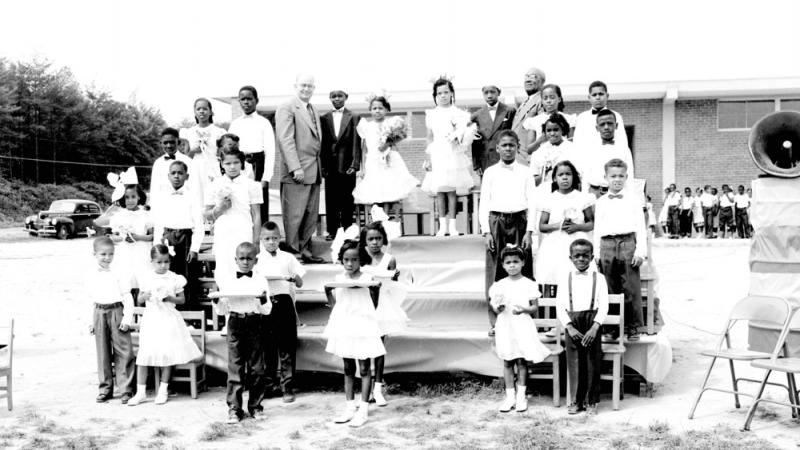 black and white photo of children standing on platform