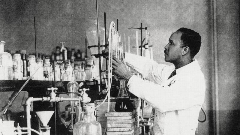 black and white photo of a man working with lab equipment