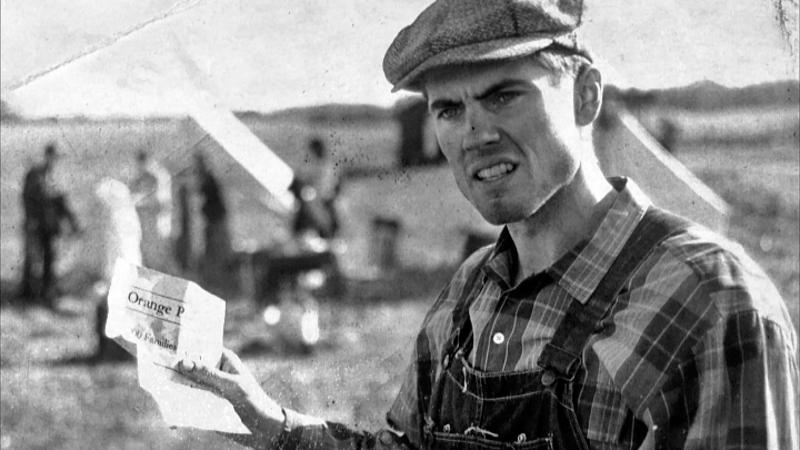 black and white film still of a man holding up a paper, wearing overalls and a hat