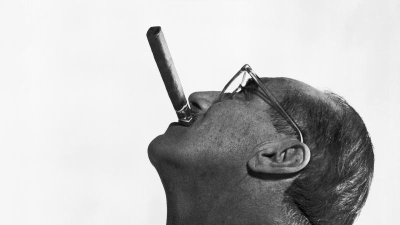 Side view of Groucho Marx, face tilted to the sky, smoking a cigar