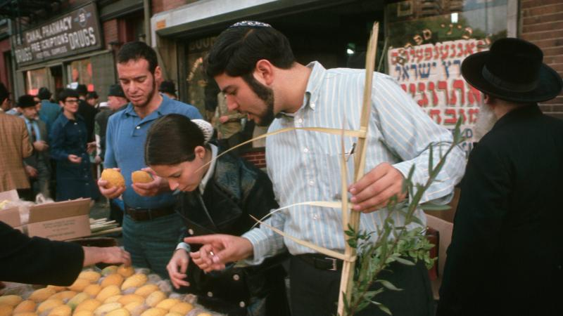 Jewish men and women look closely at produce at a sidewalk stand
