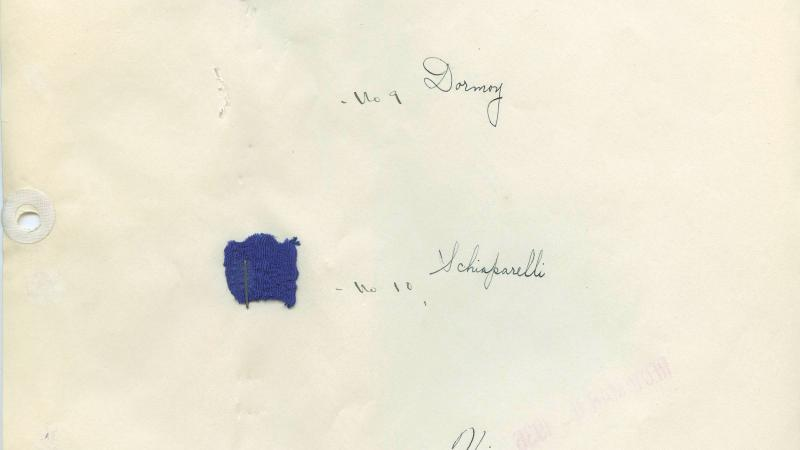 A yellowing piece of paper with small tufts of fabrics in various shades of blue, labeled in script with which fashion house it came from