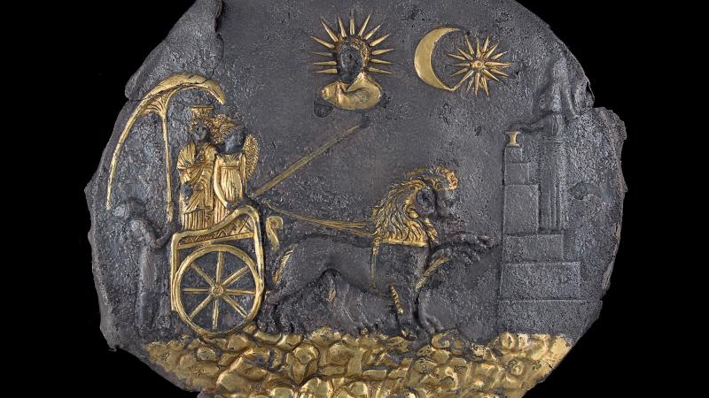 ancient plaque with gold embellishments, two figures in chariot