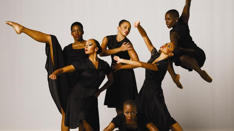 Six women dressed in black, in various dance poses