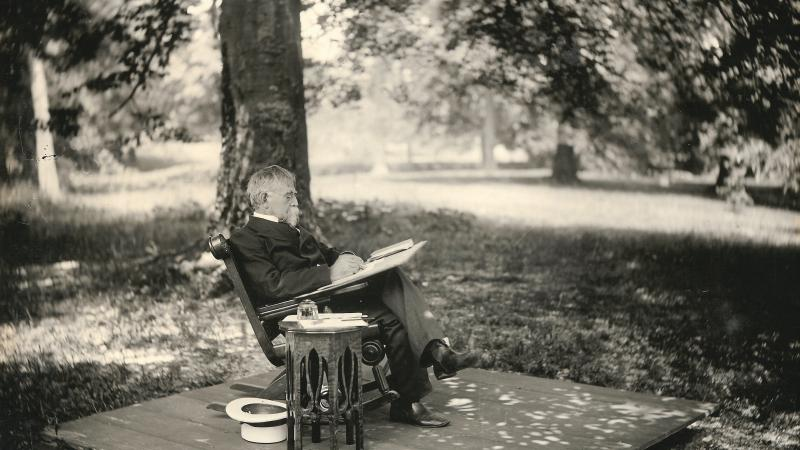 Wallace sits in a rocking chair, writing in pen on a notebook, legs crossed