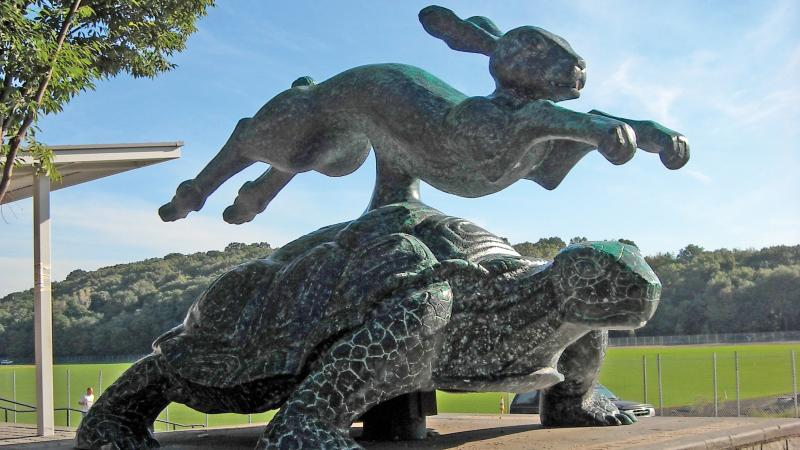A brass hare leaps over a tortoise in a larger than life sculpture