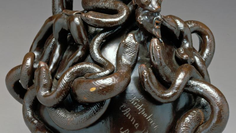 A twining mass of snakes twists around the top of a round jug with a narrow neck