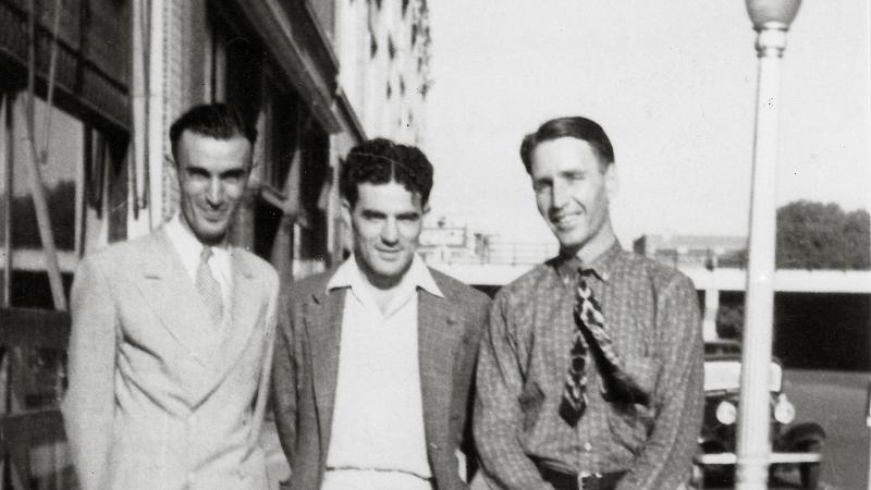 Three young men in light colored suits stand with their arms around each other; Thompson holds a straw hat