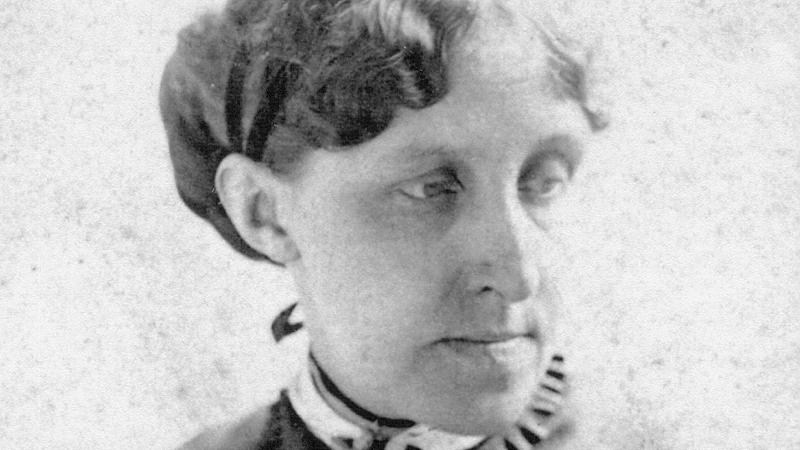 Alcott looking to her left shoulder, wearing a small ruffled collar and dark dress, with her hair in a low chignon