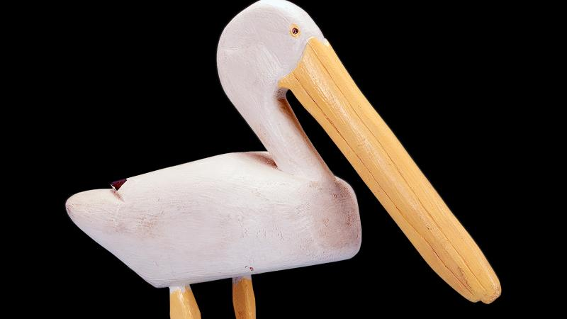 A white pelican with long yellow beak and feet, carved out of wood