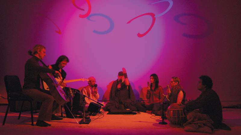 Seven performers sit in a darkened room, holding instruments, lit only by a nimbus of purple light