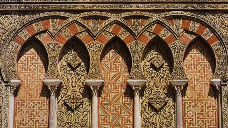 Inerlacing arches decorated with intricate floral and geometric patterns in red and gold