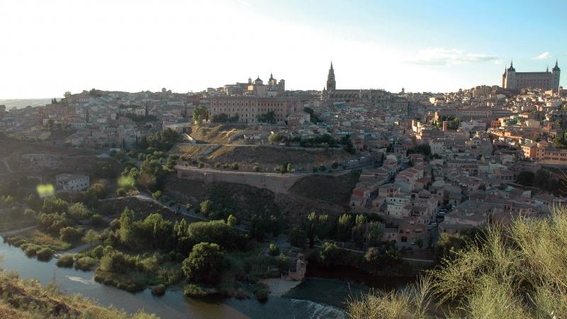View from across a river of Toledo in late afternoon sunlight