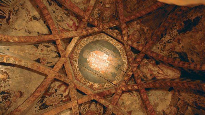 interweaving beams surround paintings of saints, decorated with gold