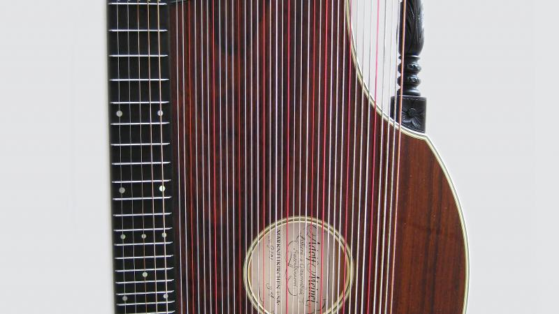 A stringed zither made of red-brown wood