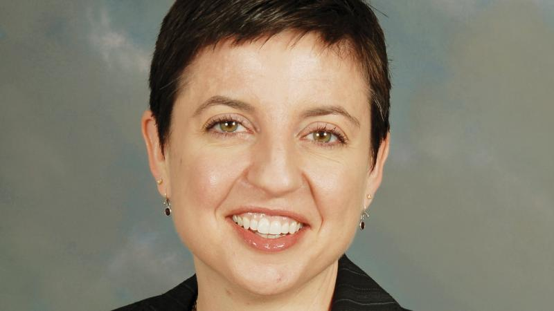 Fitzpatrick smiling, short dark hair, wearing a black blazer, maroon blouse and layered necklace with small maroon stones