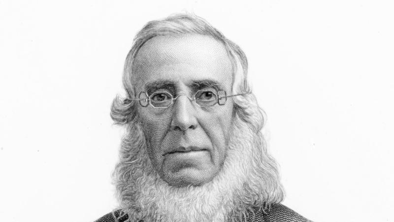 Cooper wearing octagonal eyeglasses, with a white beard no mustache, in a suit coat and bowtie