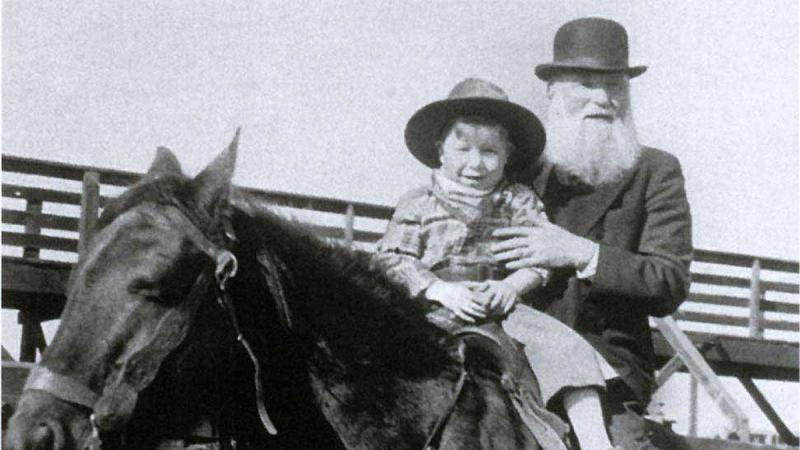Miller, bearded and wearing a bowler hat, sits behind a young boy on a horse