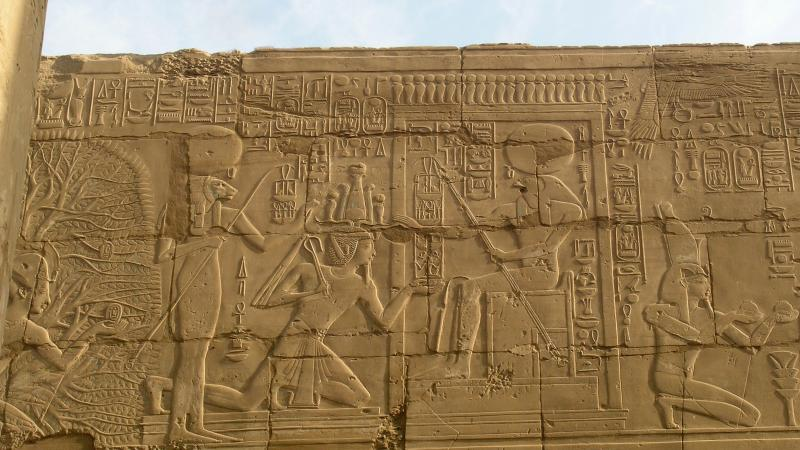 Gold colored sandstone carved with scenes of royal Egyptian life and religion