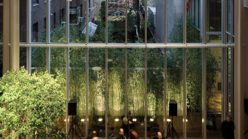 Floor to ceiling windows looking out onto a small green space bordered by tall buildings, a classical quartet plays on a stage in front of the windows