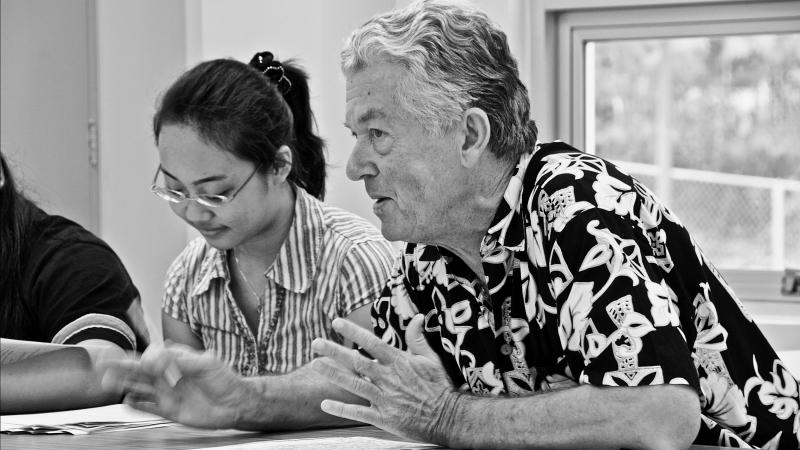 black and white photograph of a man excitedly talking at a table, a woman sits next to him