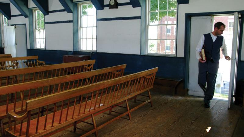 man entering an empty room filled with pews