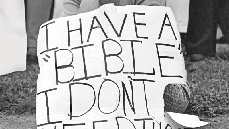 Black and white photo of a woman sitting on a curb holding a sign of protest with her chin on her fist.