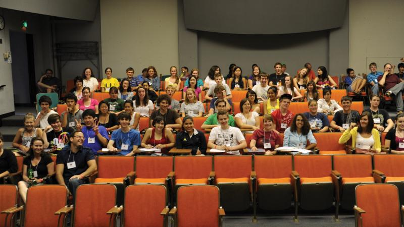Color photo of many students sitting in an auditorium, smiling.