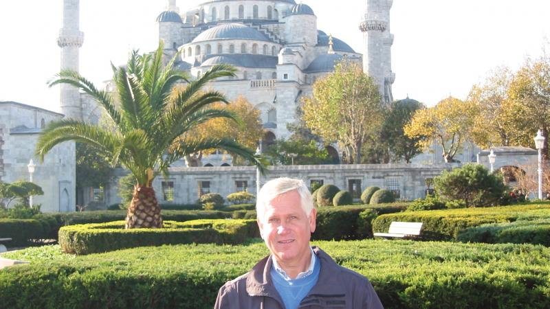 Color photo of Gale Peterson standing before a large mosque and its elaborate gardens.