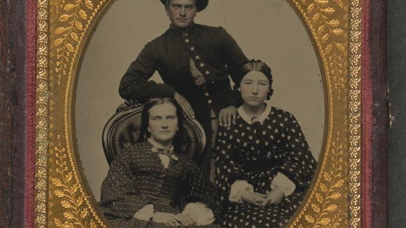 Framed black and white photo of a Union soldier posing with two women.