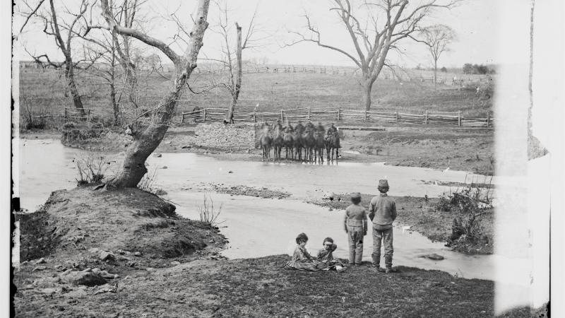Black and white photo of a creek with Union cavalry in formation on the other side.